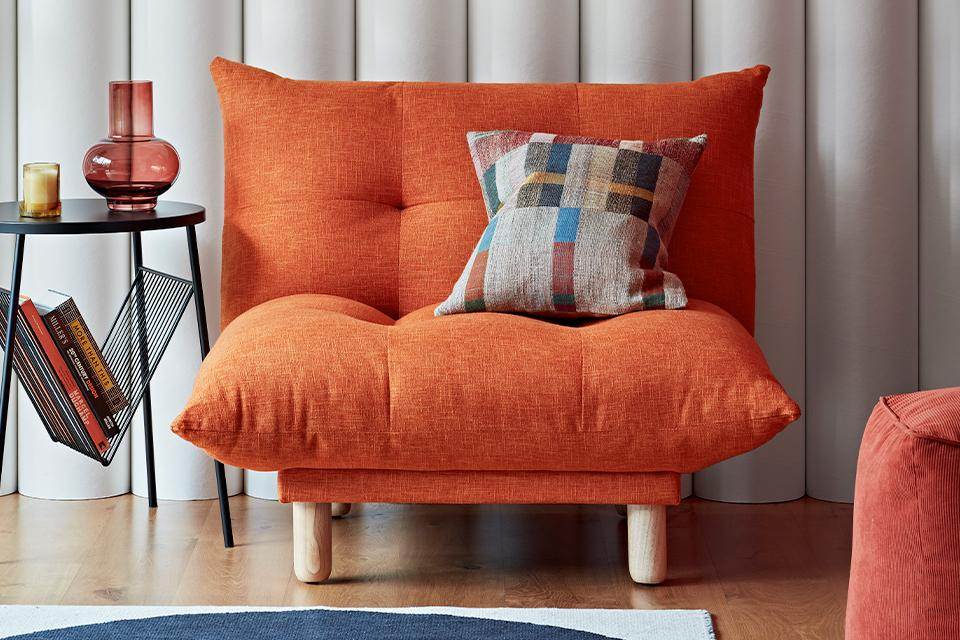Orange armchair with geometric cushion.