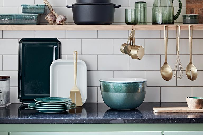 Kitchen top with green tableware and brass utensils.
