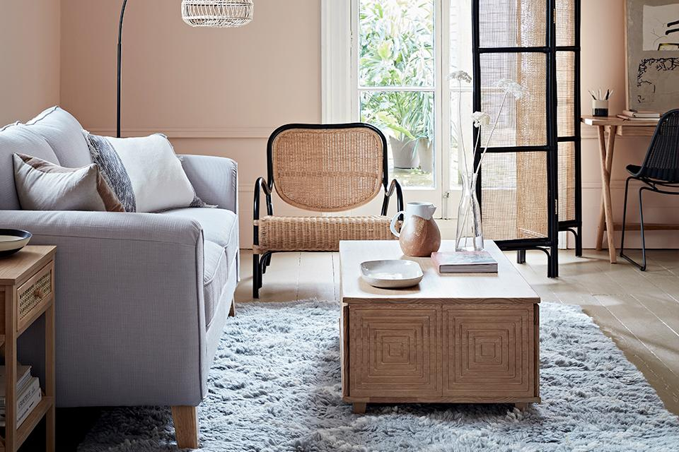 An artisan styled living room with rattan and wood accents and muted pastel colours.