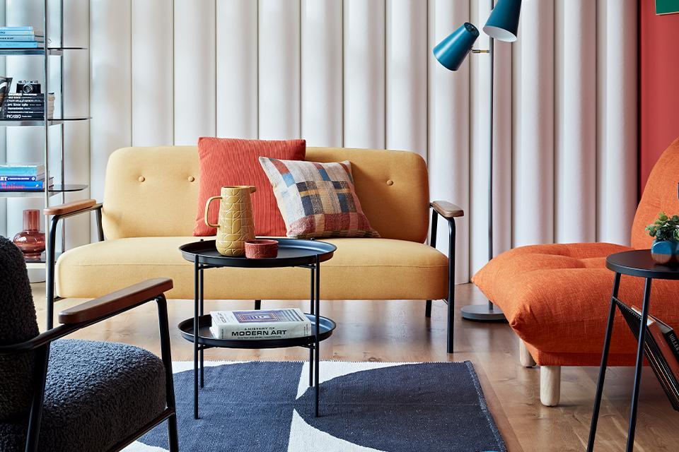 Living room with mid century yellow sofa and orange armchair.