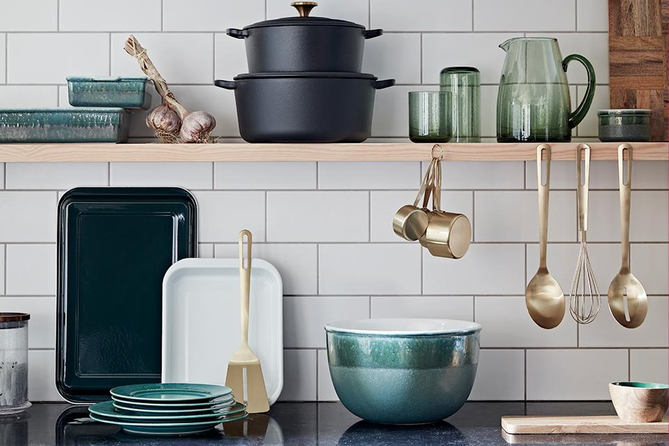 A modern country styled kitchen with blue-green stoneware and black and gold cookware.