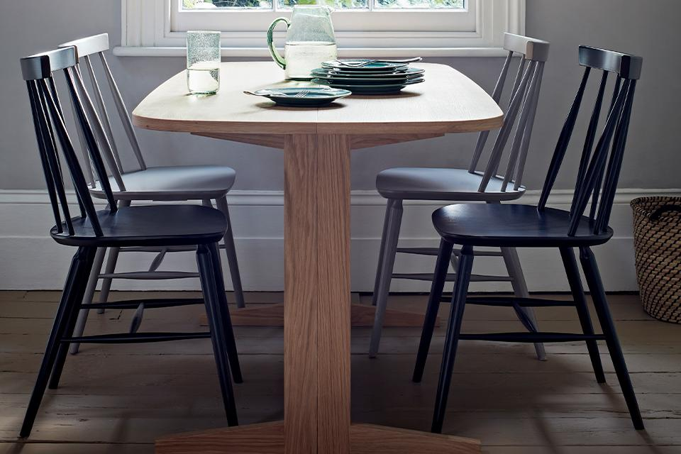 Oak dining table with black an grey dining chairs and green tableware.