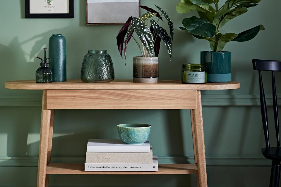 Oak console table with green vases and plants on top.