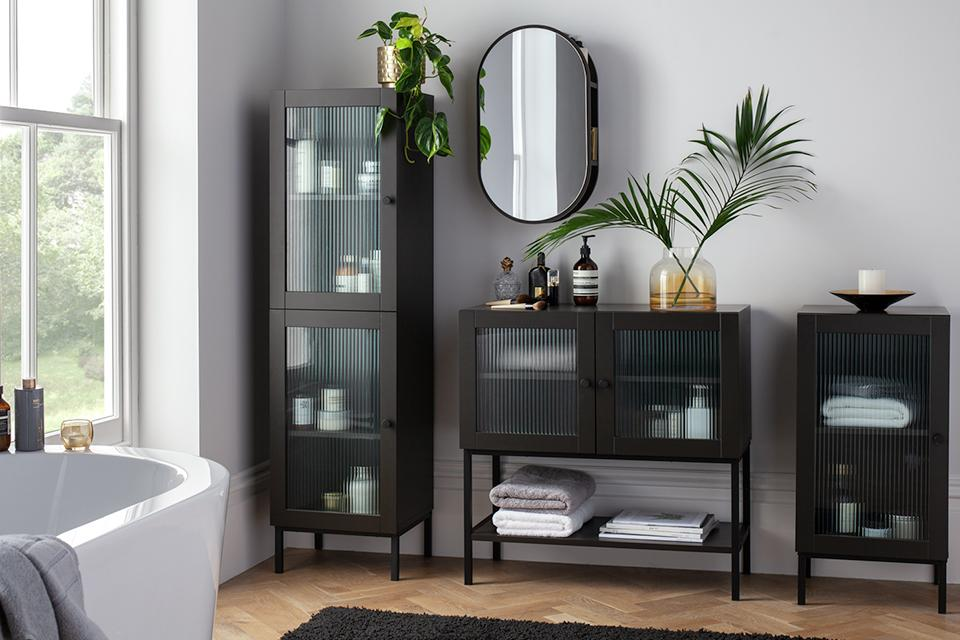 Three dark wooden bathroom storage units with textured glass fronts.