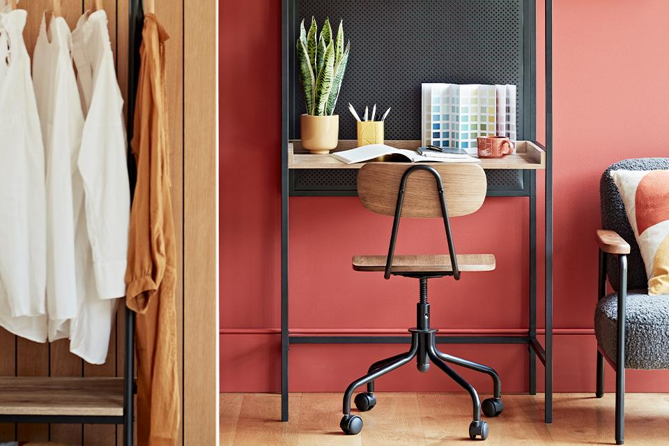 A small-space desk between a hanging rail and accent chair in a bedroom.