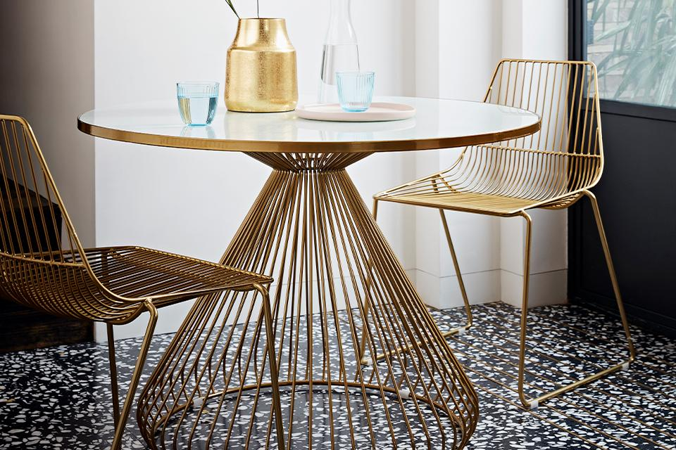 A glass-topped round gold dining table with matching chairs.