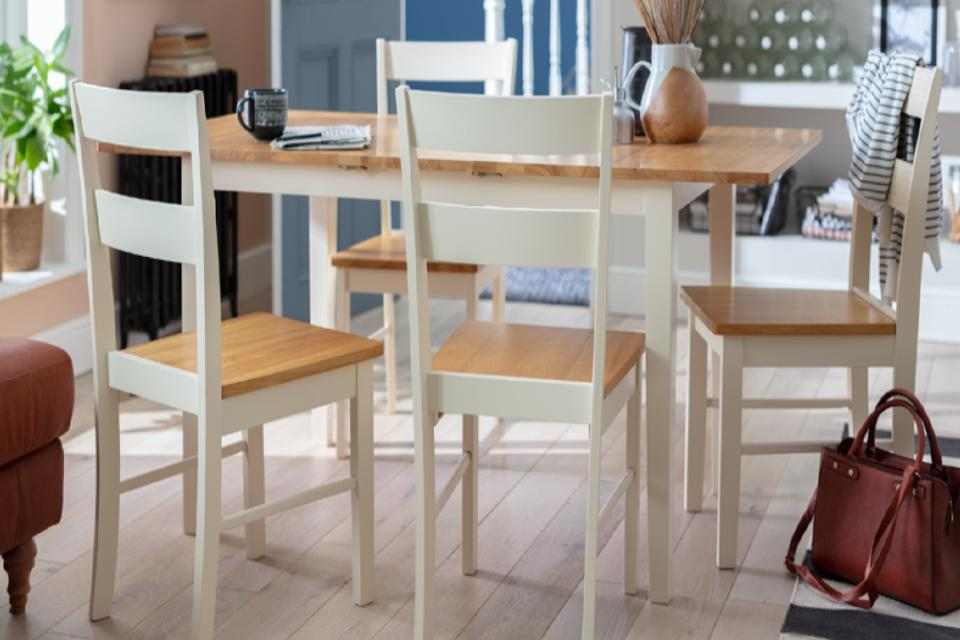 Oak and white dining tables with four matching chairs.