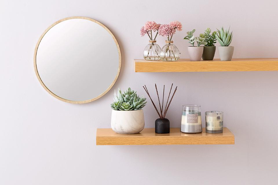 Round bamboo mirror with two wall shelves decorated with plants and candles.