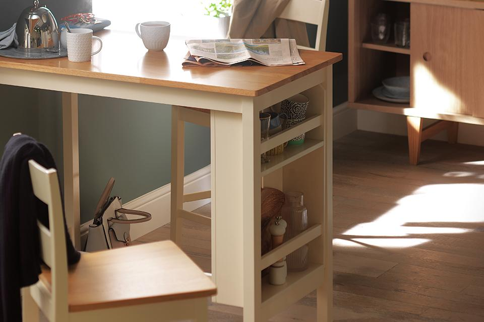 Dining table with inbuilt storage shelves and two stools.