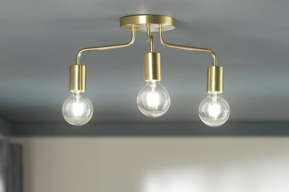 Brass ceiling light with three statement bulbs.