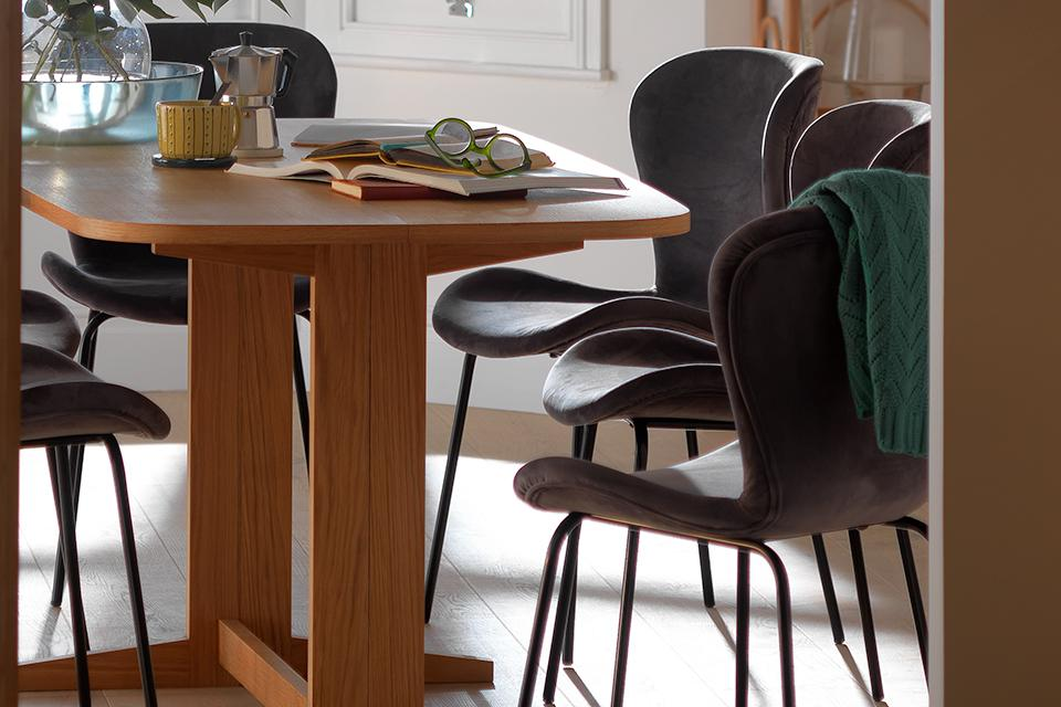 Oak extending dining table with grey velvet dining chairs.