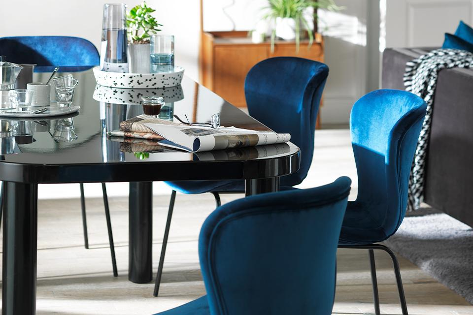 Black glossy dining table and blue velvet dining chairs.
