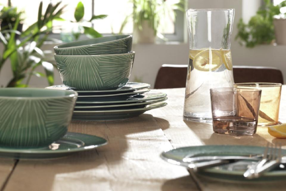 A textured set of green bowls and plates on an oak table with glassware.