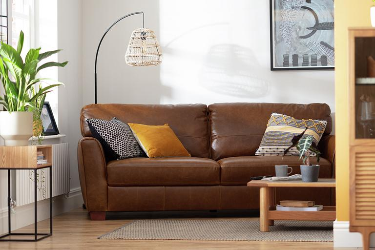 A brown leather sofa tucked into a nook in a white living room.