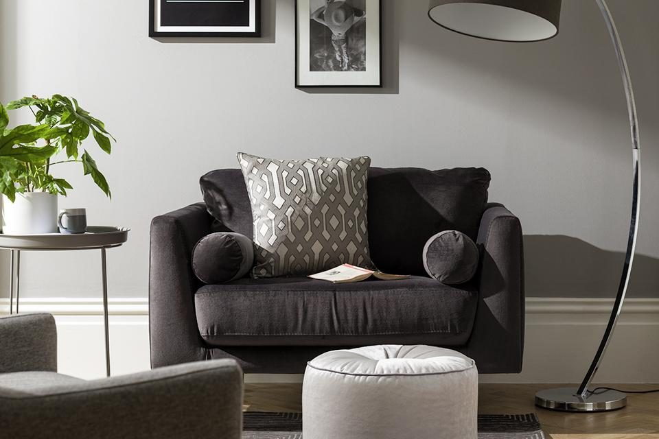 A black fabric loveseat beside a tall, arched floor lamp in pale grey living room.