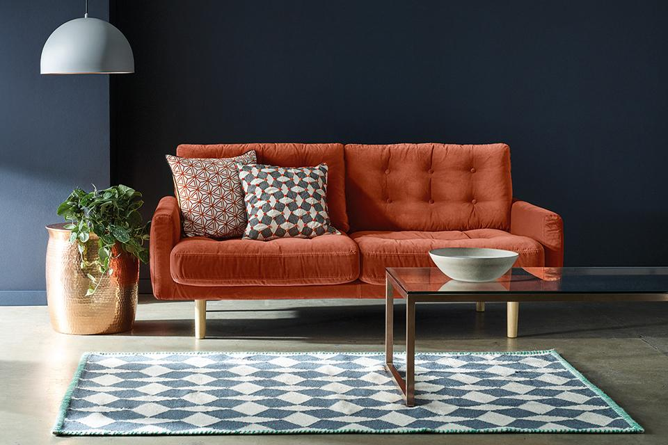 An orange velvet sofa in a charcoal grey room beside a glass coffee table and gold planter.
