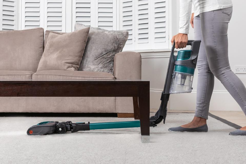 A flexible Shark vacuum bending under the coffee table.
