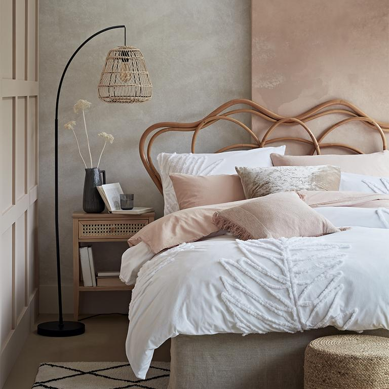 An artisan style bedroom with boho vibes from rattan accents and a soft colour palette.