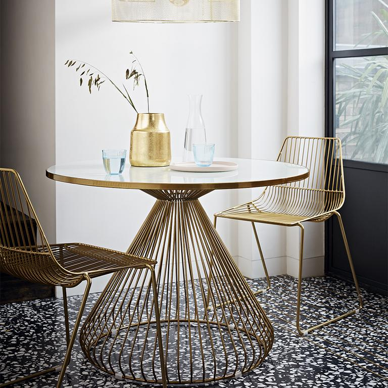 A gold and glass-topped round dining table with matching chairs and decor.
