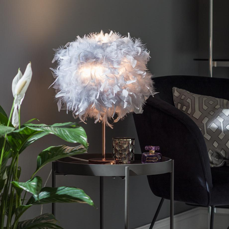 An image of a table lamp with a grey, feather shade.