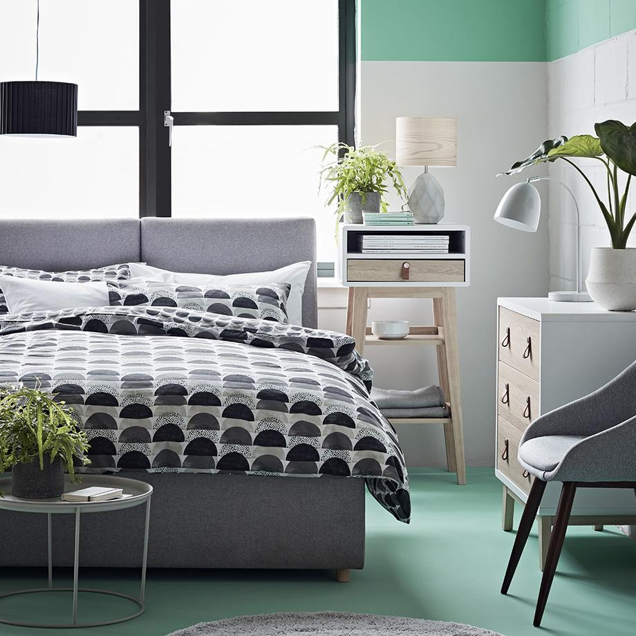 Bright bedroom with scandi-style furniture, a geometric monochrome duvet set and decorated with green highlights.