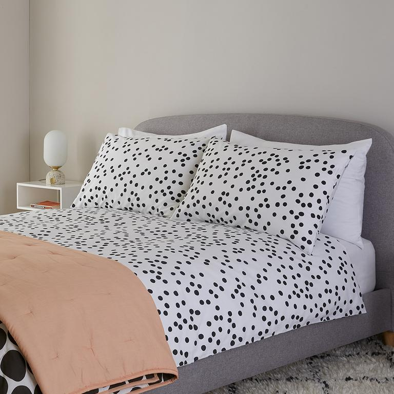Image of black and white polka dot bedding with a blush pink throw.