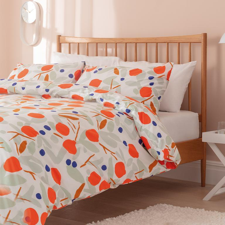 Image of orange, beige and blue patterened bedding.