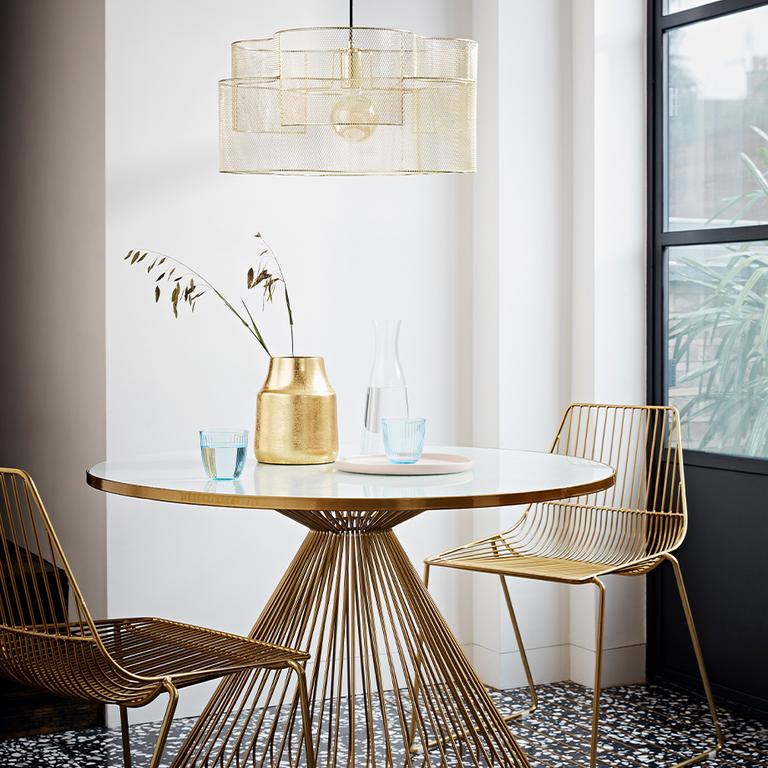A glass-topped gold table with matching gold wire-backed chairs.
