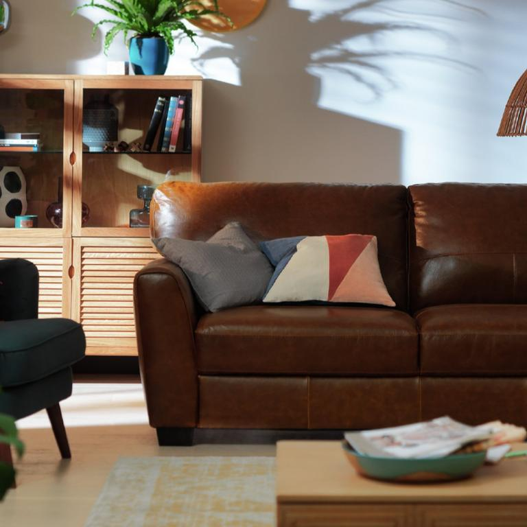 A brown leather sofa with mismatching cushions.