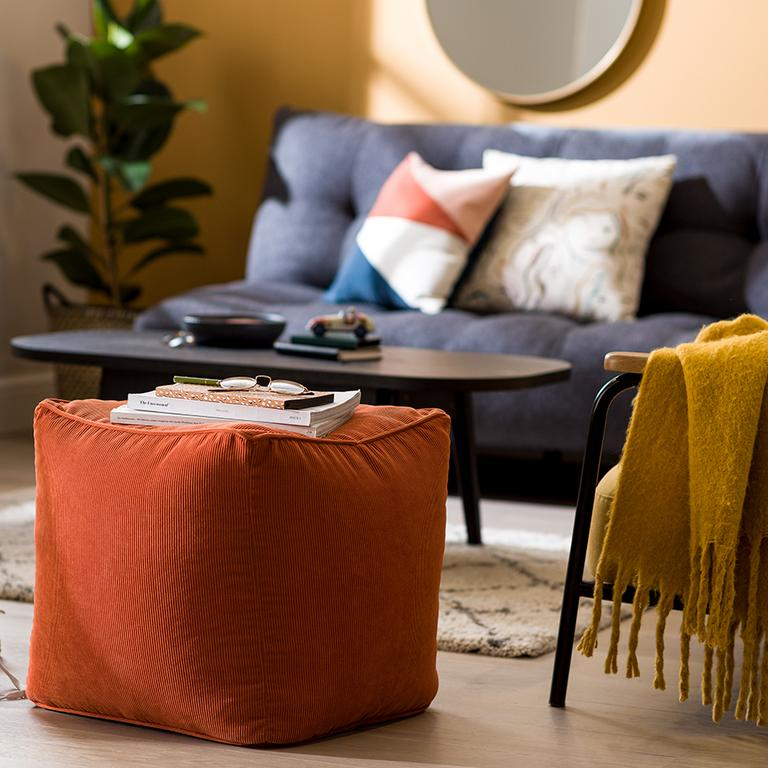 An orange footstool surrounded by mid-century style furniture and accessories.