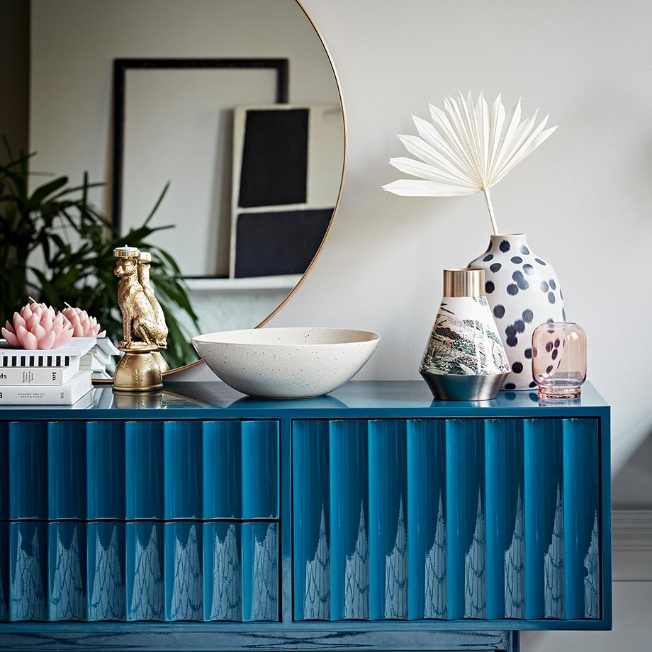 A bright blue sideboard decorated with ornaments beneath a large round mirror.