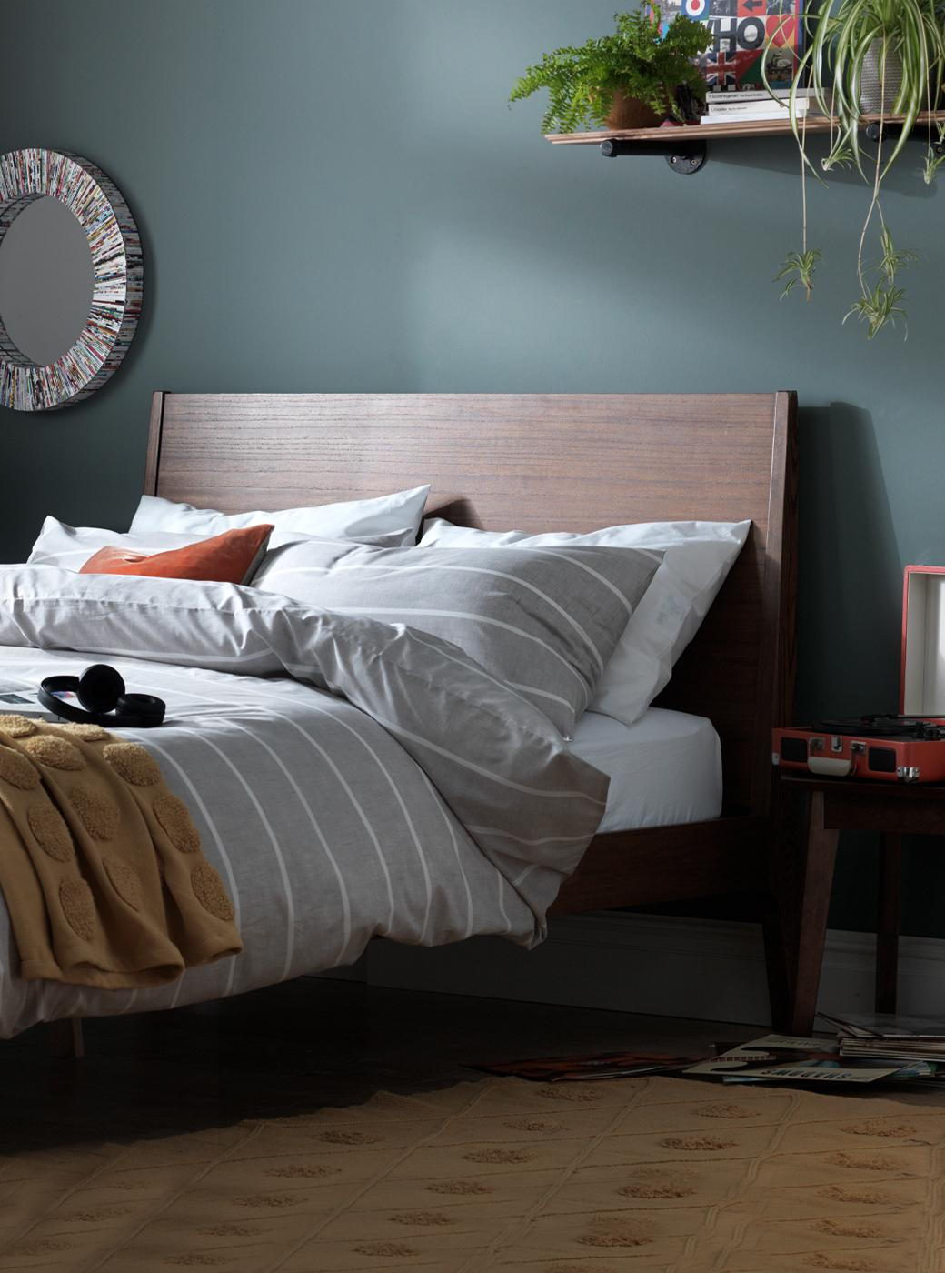 Dark wooden bed frame, with a grey duvet set.
