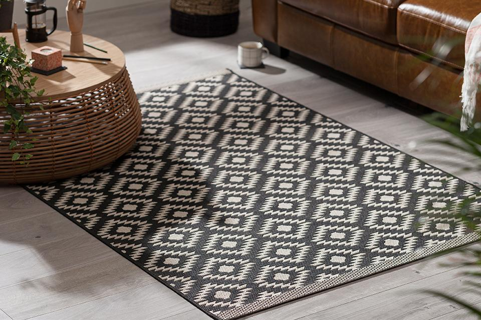 Black and white diamond patterned rug in front of sofa.