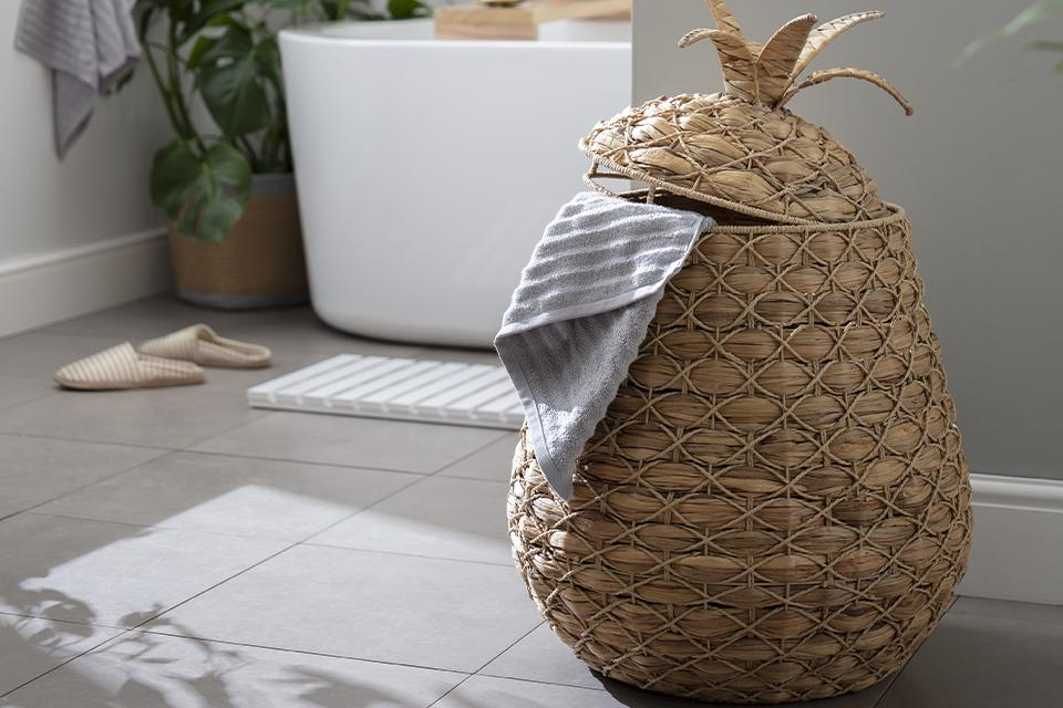 Pineapple shaped laundry basket with bathtub in the background with indoor plant, bath rack, bathmat and slippers.
