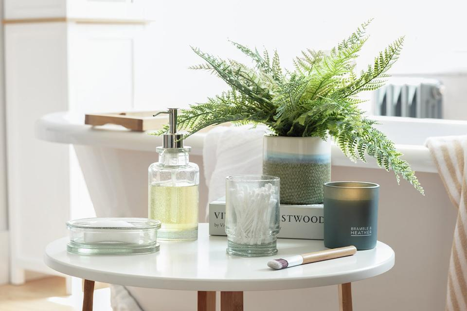 Side table next to a white bath with indoor plant, candle, book, pump bottle placed on the table.