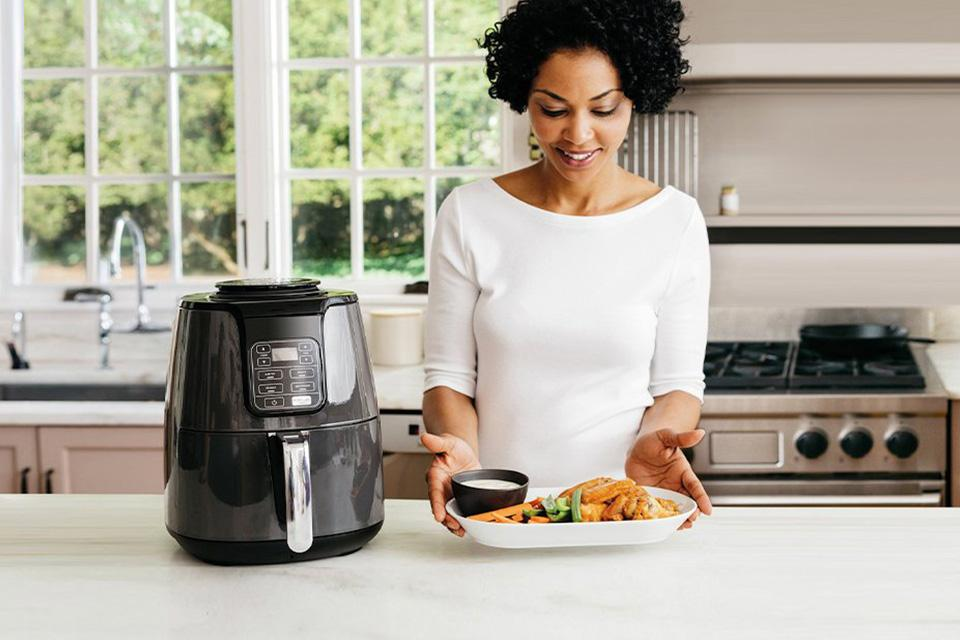 Woman using multi-cooker to prepare healthy meal.