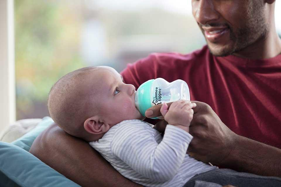A baby being bottle-fed by a man.