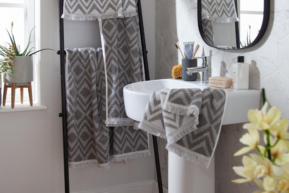 Grey and white diamond pattern towels hung on a black ladder shelf.