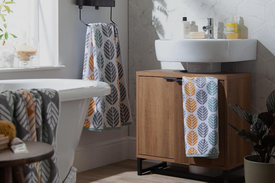 Brightly coloured leaf print towels in a white bathroom with wooden accents.