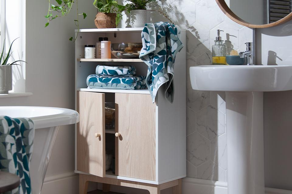 A white and natural wood bathroom cabinet containing essentials and decorative plants.