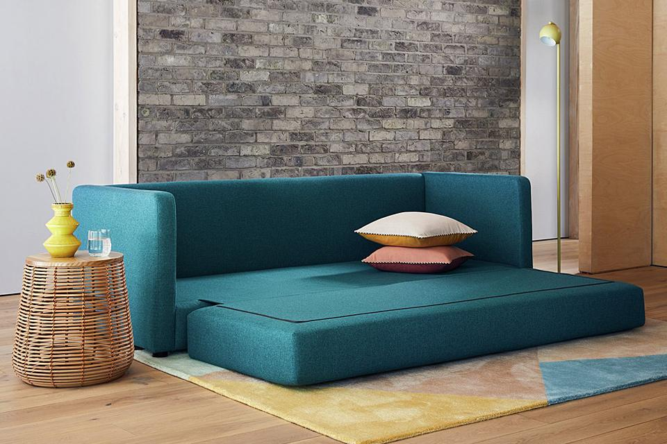 Modern green sofa bed, folded out, ready for guests.
