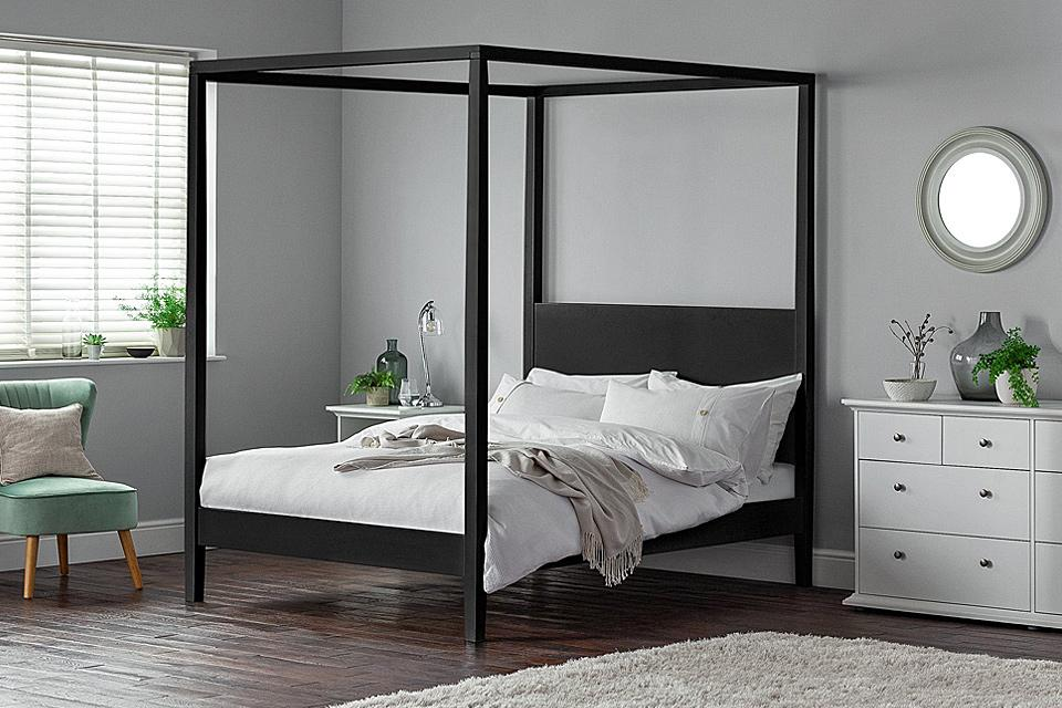 Modern black four poster bed in a bright bedroom.