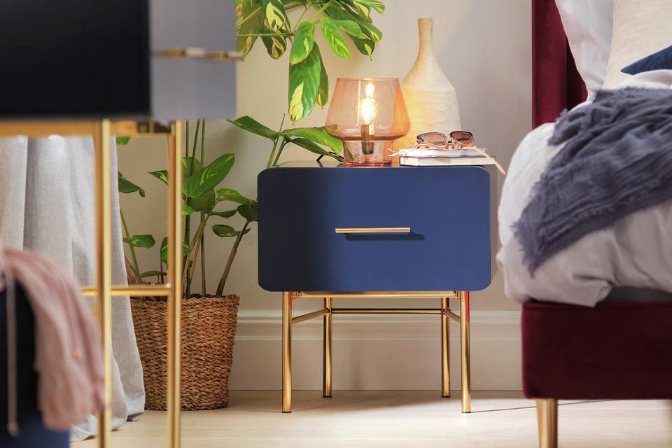 A blue bedside table with gold legs and handle in a cosy bedroom.