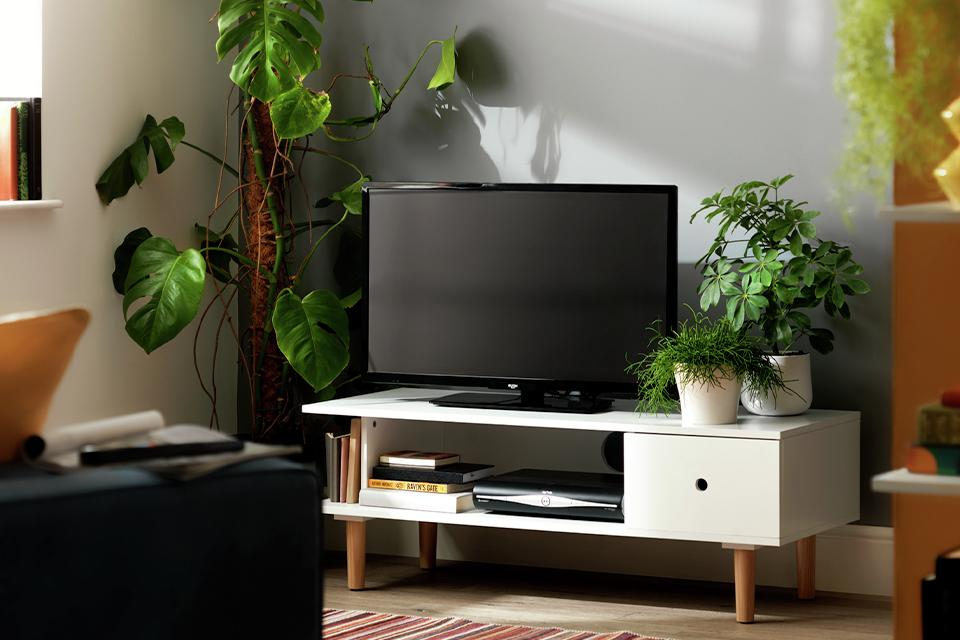 A television on a white TV stand between indoor plants.