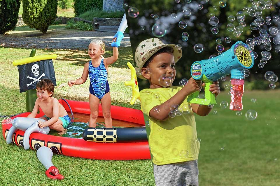 Two children playing in a pirate ship themed paddling pool and a little boy playing with a bubble gun.
