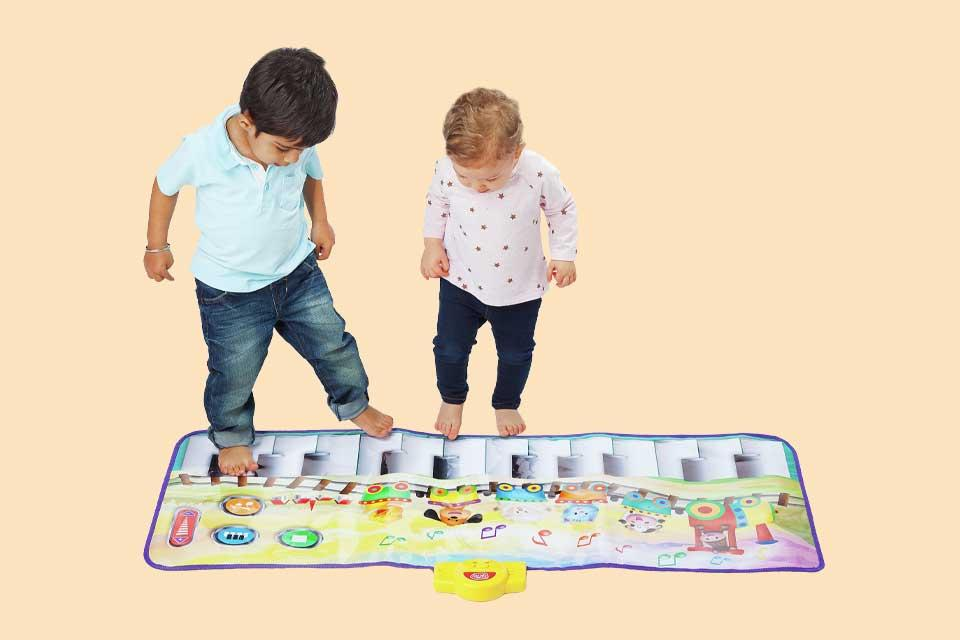 Two toddlers standing on a large floor piano mat.