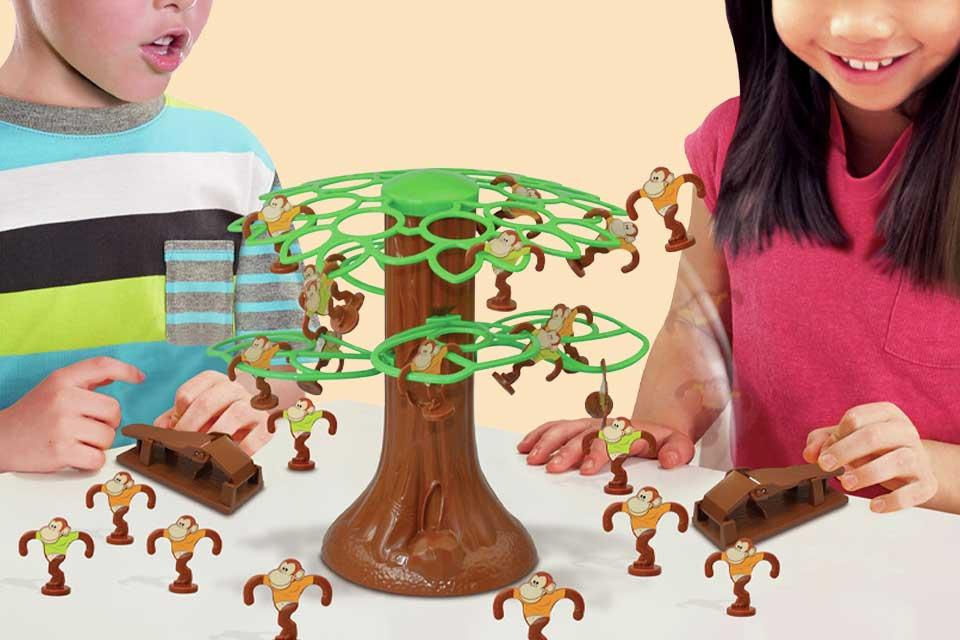 Image shows two children playing a board game involving monkeys in a plastic tree.