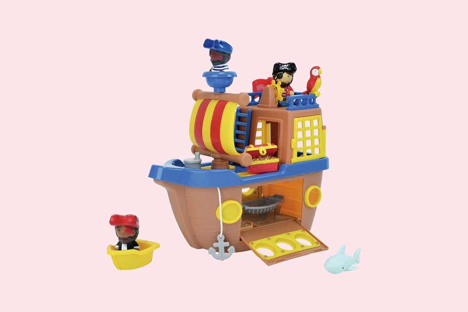 A toddler plays with a Tots Town pirate ship playset.