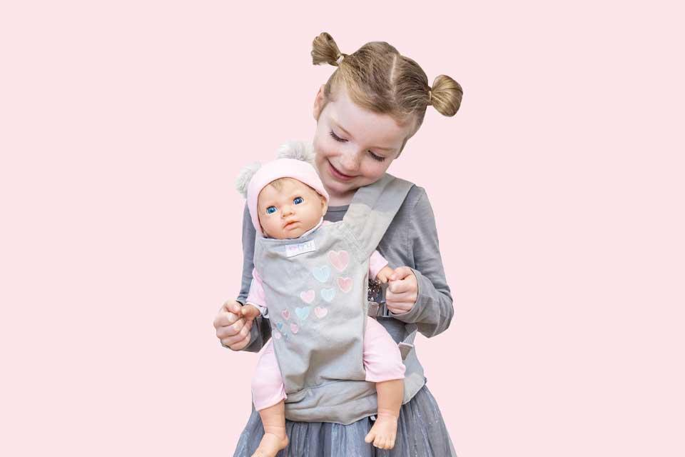 Image shows a small girl carrying a Tiny Treasures doll in a baby sling.