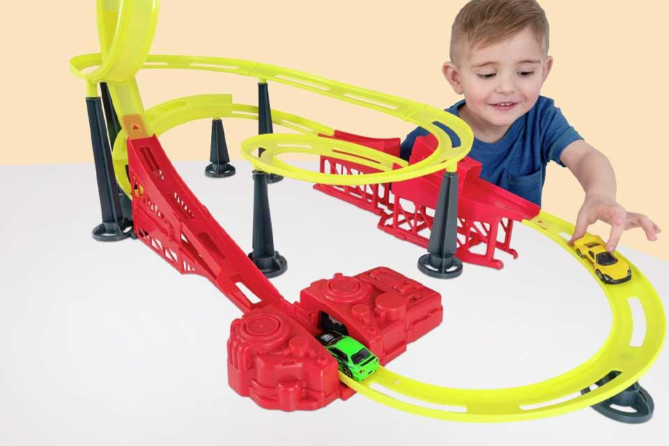 A small boy is playing with a red and yellow toy car track, with steep bends and loops.